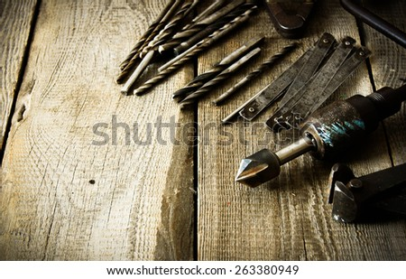 The old working tool. Old drill, compasses, ruler and drills on a wooden background. - stock photo