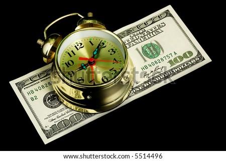 The oldfashioned alarm clock on money. Isolated on black. - stock photo