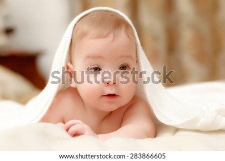 The one baby seven-month  smiling girl covered with a white towel in bed on white sheets