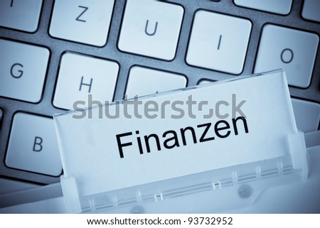the one hanging folder tab before a computer keyboard on finances
