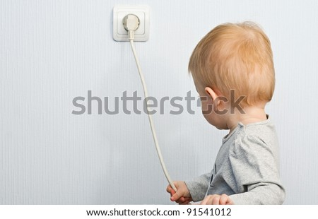 The one-year-old child pulls for an electric wire - stock photo