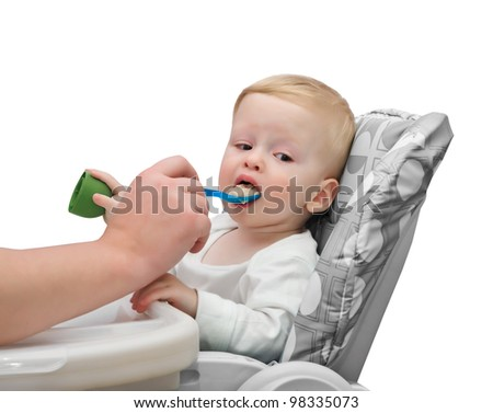 The one-year-old kid eats porridge - stock photo