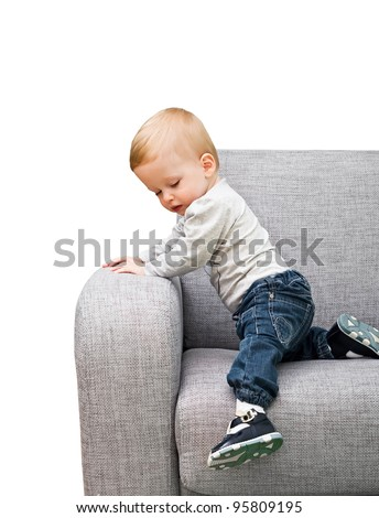 The one-year-old kid learns to climb down from a sofa - stock photo