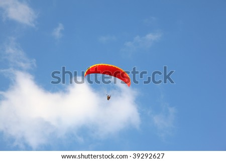 The operated red parachute flies in high in the blue sky