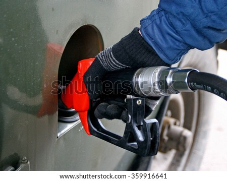 the operator refuels the car with petrol at a gas station