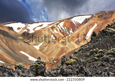 The orange and beige rhyolite mountains with snow in the hollows. National Park Landmannalaugar in Iceland. Pieces of gray and black lava, sometimes covered with green moss. - stock photo