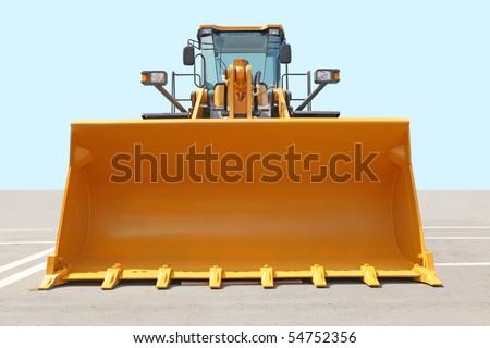 The orange bulldozer on a concrete platform against the sky - stock photo