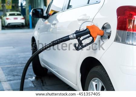 The orange color fuel nozzle filling oil into the white car - stock photo