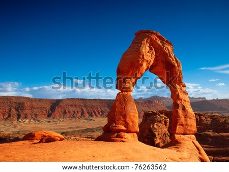 The orange color of Utah's Delicate Arch contrasted against a deep blue sky. - stock photo