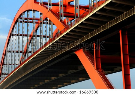 The orange colored steel cable stayed bridge high in  the blue sky. - stock photo