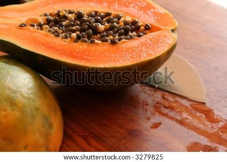 The orange flesh and black seeds of a freshly cut papaya. - stock photo