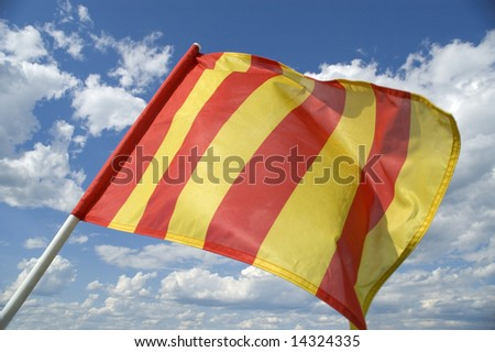The orange striped flag on a background of the dark blue sky with clouds is yellow .