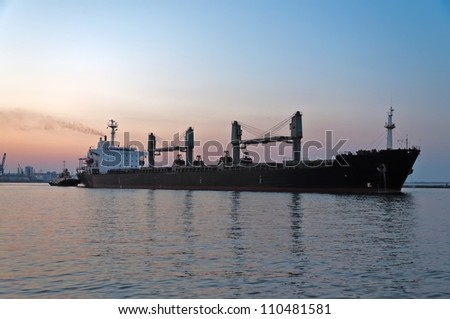 The ore carrier heaves out of the harbor on a tow, the photo is taken at sunset. - stock photo
