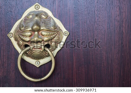 the oriental door handle , Old Chinese style door handle on the dark wood background ,Chinese Brass Hardware - stock photo