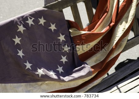 The original 13 colonies American flag laying on a wooden bench. - stock photo