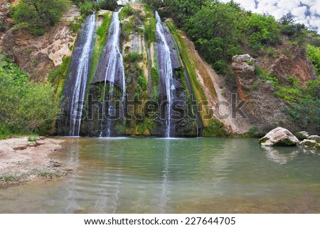 The original three-jet Falls on the border of Israel. Three parallel streams of water running down the steep slope and fall in oval pool - stock photo
