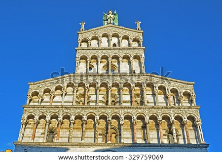 The ornate western facade of St Michele church, Lucca, Italy, with the archangel on the apex - stock photo