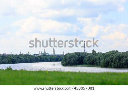 The Orthodox Church stands on the banks of the river, summer, trees, grass.