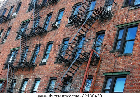 The outside wall of an apartment block featuring fire escapes in New York City. - stock photo