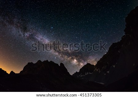 The outstanding beauty of the Milky Way arc and the starry sky captured at high altitude in summertime on the Italian Alps, Torino Province. Fisheye scenic distortion and 180 degree view. - stock photo