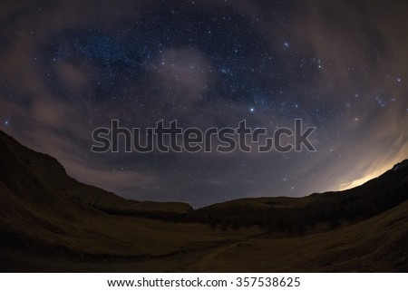 The outstanding beauty of the starry sky and Milky Way in winter season, captured from black conifer woodland. Scenic distortion due to fisheye lens, acceptable digital noise due to 1600 iso setting. - stock photo