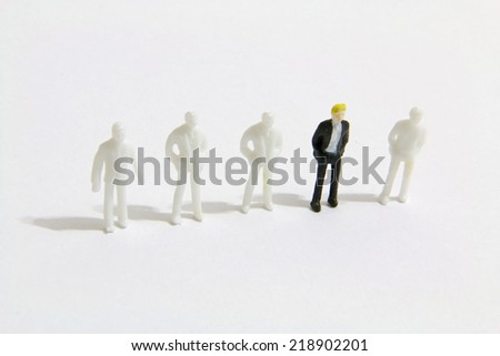 The outstanding miniature business people standing with other  miniature people on the white background - stock photo