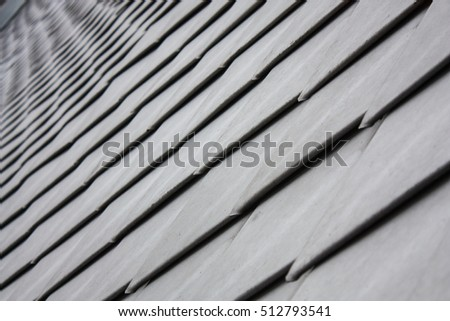 the overlapping metal roof tiles on a church rows fading out of focus in the background