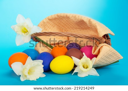 The overturned basket with eggs and white flowers on a blue background - stock photo