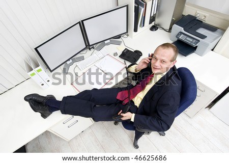 The owner of a small business relaxing behind his desk making several phone calls - stock photo