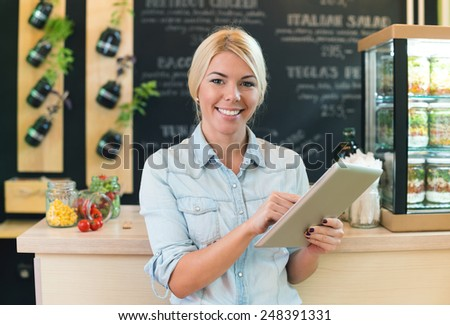 The owner of small restaurant holding a digital tablet - stock photo