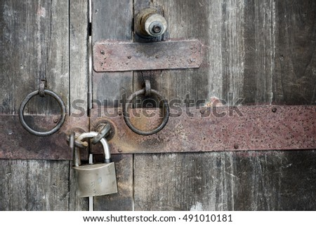The padlock locking the old wooden door