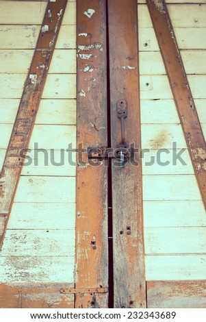 The padlock on an old wooden door background - stock photo