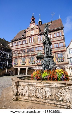 The painted facade of the town hall and a fountain with a statue of Neptune in front of it, Tubingen, Germany. - stock photo