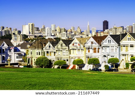 The Painted Ladies of San Francisco, California sit glowing amid the backdrop of a sunset and skyscrapers.