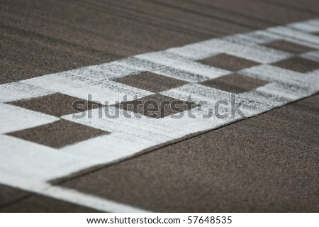 The painted start/finish line across the track at the Rockingham motor speedway in Northamptonshire, UK. Black tire marks are streaked across the track. Shallow focus is on the near part of the line. - stock photo