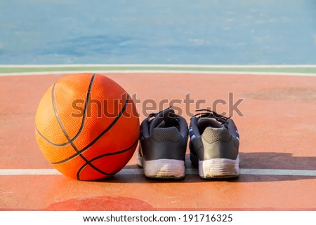 The pair of sport shoes and basketball ball On the cement floor - stock photo
