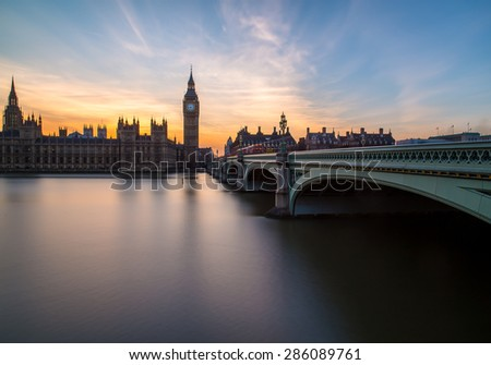 The Palace of Westmisnter at Sunset from across the River Thames. Part of Westminster Bridge can also be seen. - stock photo