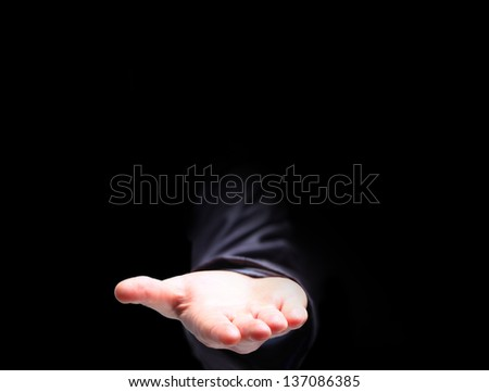 The palm of the hand to the top, on a black background. - stock photo