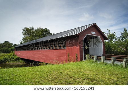 The Paper Mill Covered Bridge sparkles against a bright blue sky in Bennington County, Vermont. - stock photo