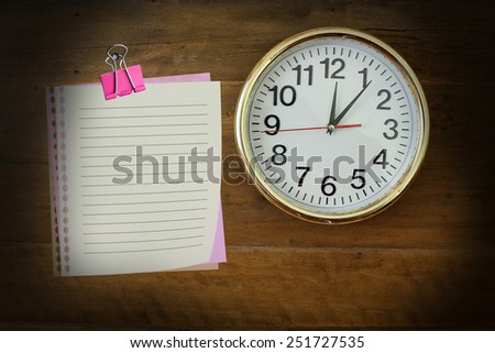 The paper  with  twelve  o'clock hanging on the wooden wall. - stock photo