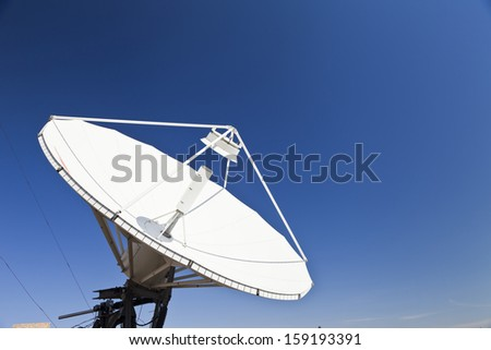 The parabolic antenna against the blue sky in the bright sunny day - stock photo