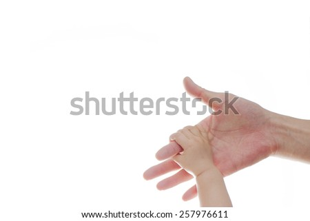 The parent's hand holds on one year old baby's hand close up over white in studio as background - stock photo