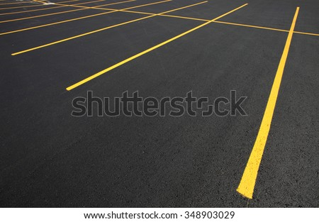 The parking stalls in a parking lot, marked with yellow lines. - stock photo