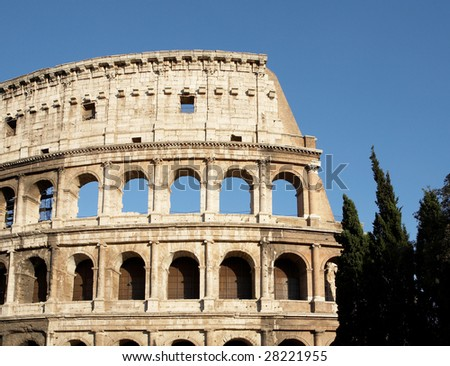 The part of Colosseum wall with trees on blue sky background