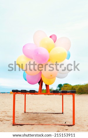 The party is over. Bunch of colored balloons attached to bench on the beach. Outdoors. - stock photo