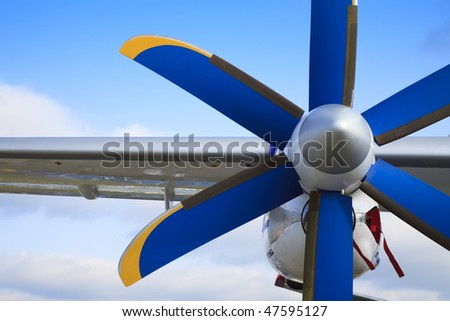 The passenger plane,  blue and yellow propeller - stock photo