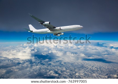 The passenger plane in flight. Aircraft flies high in the blue sky over clouds.