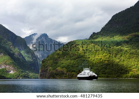 The passenger ship going in fjords, between high rocky coast, Norway