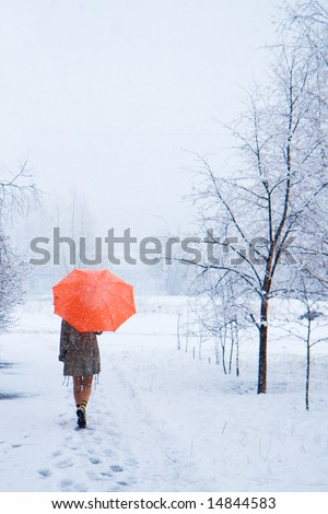 The passerby with an orange umbrella in snow park - stock photo