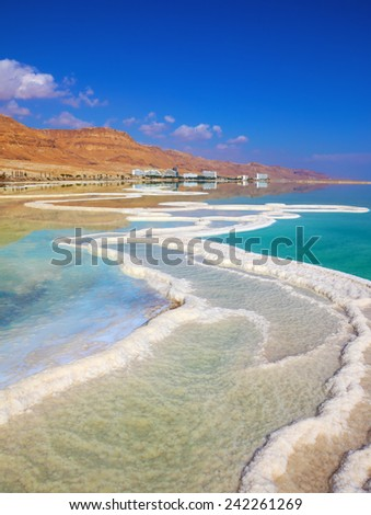 The path from salt picturesquely curls in salty water. Hotels are reflected in smooth water ashore. Israeli coast of the Dead Sea - stock photo